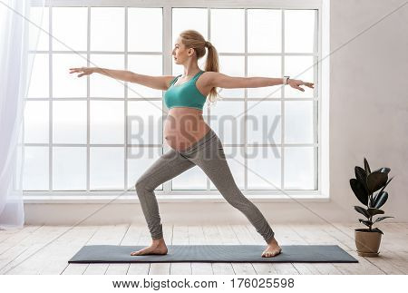 Joyful yoga. Full length portrait of happy healthy pregnant woman standing indoors in workout clothes and doing exercises