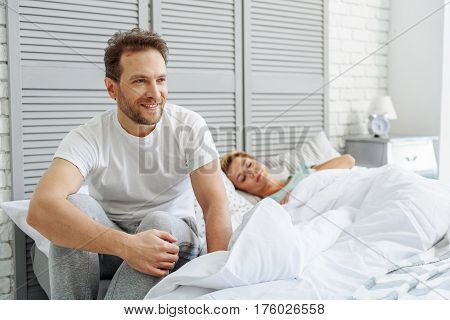 I am happy at my home. Portrait of cheerful man sitting on bed and smiling. His wife is sleeping on background