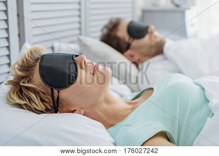 Calm woman is sleeping at home with pleasure. She has eyewear on her eyes. Her husband is lying on background