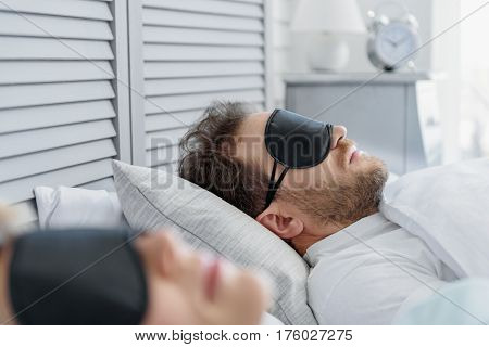 Serine middle-aged man is napping on bed near his wife. He is wearing mask for sleep poster