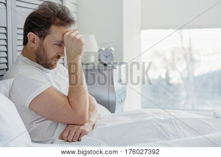 Pensive man is making serious decision. He is sitting on bed and touching forehead with desperation