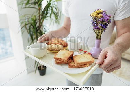 Romantic breakfast in bed. Close up of male hands holding tray with fresh pastry, cups of coffee and flowers