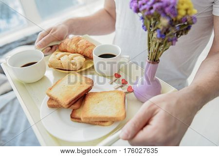 Top view close-up of man carrying tray with toasts, croissants, cups of coffee and bouquet in bedroom