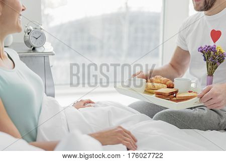 Enjoying morning together. Cheerful married couple is sitting on bed at home. Man is holding tray with hot drink and pastry. Man is smiling with happiness