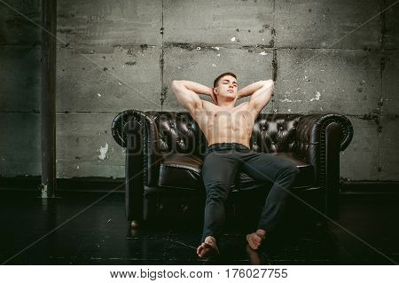 Young Sexy Men Bodybuilder Athlete Sitting On A Black Leather Couch With A Naked Torso And Black Tro