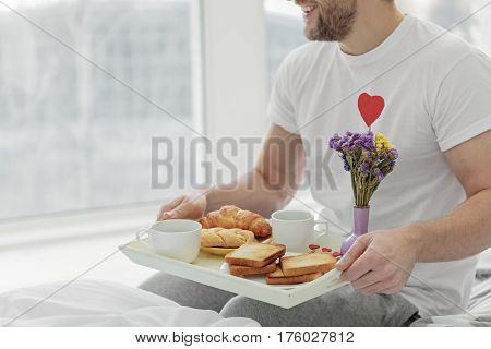 My heart is full of love. Happy man is bringing romantic breakfast to bed. He is sitting and laughing