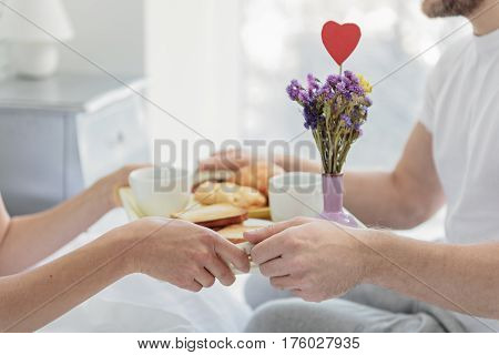 Close up of happy loving couple having romantic breakfast in bedroom. Focus on their hands holding tray with hot drink and toasts