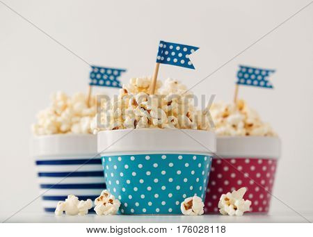 Homemade buttered popcorn served in colorful bowls decorated with party flags. Popcorn arranged in striped and spotted bowls.