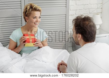 Portrait of excited woman receiving present from her husband. She is sitting on bed and smiling
