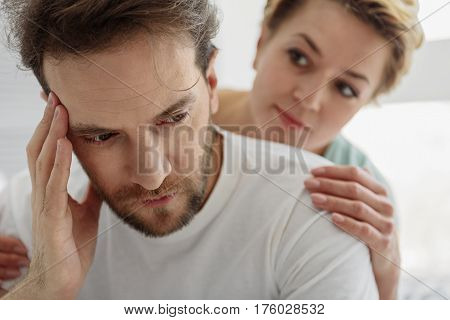 Portrait of upset man has troubles at work. His wife is trying to calm him down while looking at him with compassion