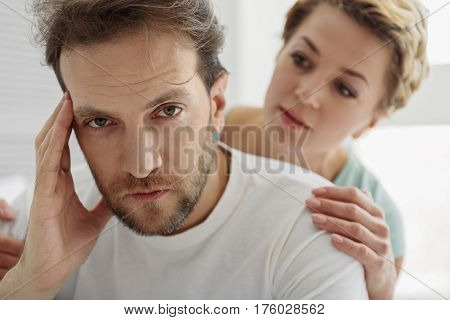 What happened. Portrait of frustrated man looking at camera with sadness. His wife is supporting him with sympathy