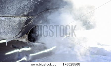 Car pipe puffs out exhaust gas clouds. Smoke clouds coming out of automobile tailpipe. Air and environment pollution by vehicle closeup shot.