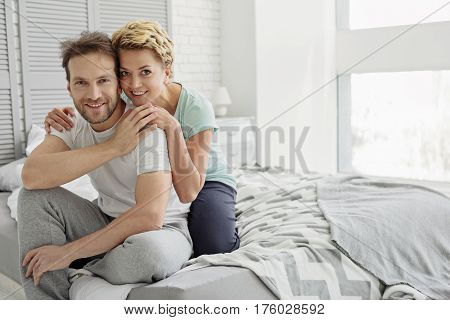 We are happy together. Cheerful married couple is sitting on bed and hugging. They are looking at camera and smiling