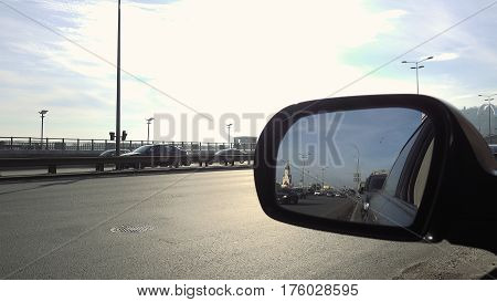 Rearview mirror of the car. View in rear view mirror of city street on the day rush hour traffic. Cars and vehicles on the road.
