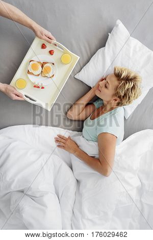 I prepared breakfast for you. Top view of joyful woman is looking at tray with fried egg toasts and juice in male hands. She is lying on bedding and smiling