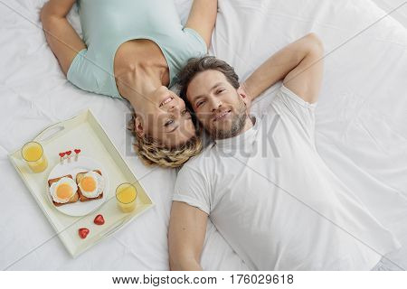 This is wonderful morning. Relaxed married couple is luxuriating on bed and smiling. Tray with healthy romantic breakfast near them. Top view