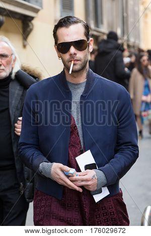MILAN ITALY - FEBRUARY 25: Fashionable man poses outside Blumarine fashion show during Milan Women's Fashion Week on FEBRUARY 25 2017 in Milan.
