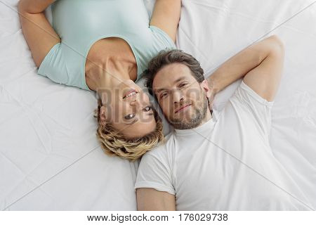 Top view of happy loving couple lying on bed and relaxing. They are smiling