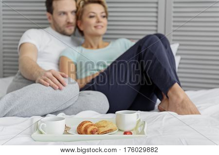Romantic breakfast in bed. Focus on croissant and cups of coffee on tray. Happy man and woman are sitting and hugging on background