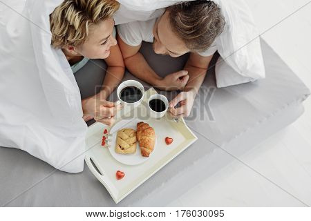 Lets hide from everyone and be only together. Top view of excited loving couple drinking coffee with pastry in bed. They are looking at each other and laughing