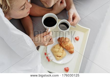 Sensual man and woman are enjoying espresso in bedroom. Top view