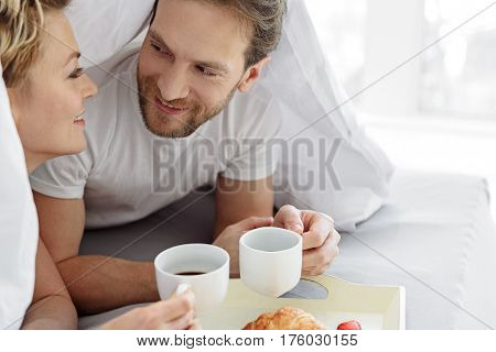 Perfect morning. Happy loving couple is having breakfast in bed. They are lying under blanket and smiling