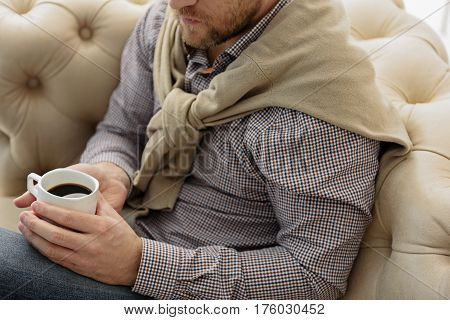 Calm man is relaxing with coffee. He is sitting on couch