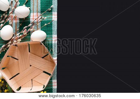 Easter mockup. White eggs unpainted, pattern for your colors, and empty basket on napkin at black background decorated with pussy willow spring flowers. Top view with copy space