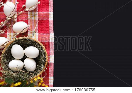 Easter mockup. White eggs unpainted, pattern for your colors, in bowl on napkin at black background decorated with mimosa and pussy willow spring flowers. Top view with copy space