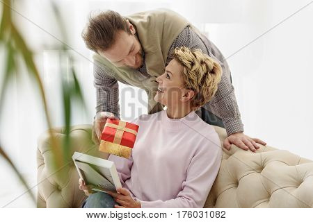 This present is for you. Cheerful man is giving colorful box to his wife. Woman is sitting on sofa and holding photo frame. They are looking at each other and laughing