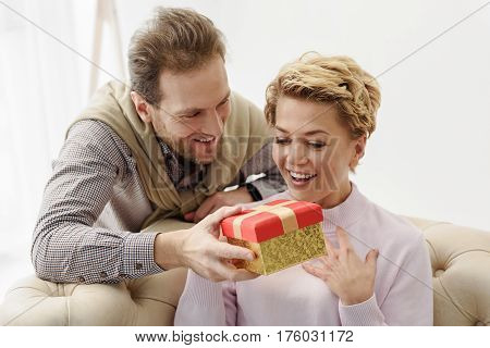 What a wonderful gift. Joyful woman is looking at box in male hands with surprise. She is sitting on sofa and smiling