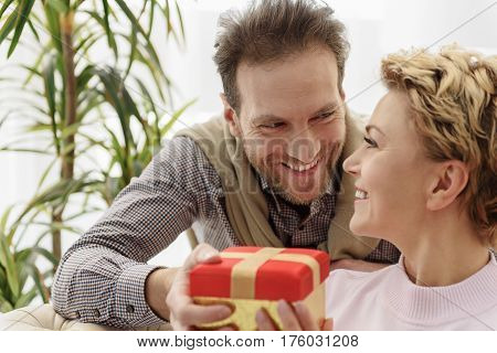 Happy man is greeting his wife with anniversary. He is giving present box to her and smiling. Woman is sitting and looking at husband with love
