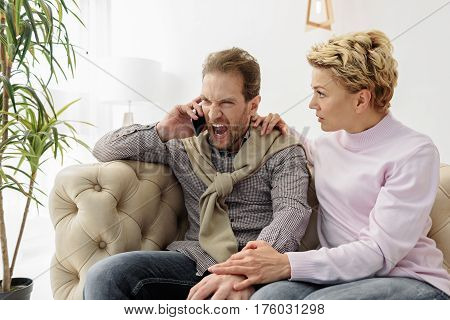 Angry man is talking on phone and shouting his interlocutor. Woman is sitting on couch and looking at husband with shock