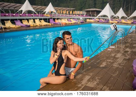 Beautiful Couple Man And Woman Sitting On The Edge Of Swimming Pool At The Luxurious Resort And Maki