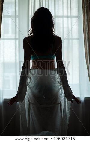 Lady standing near window. Woman taking off nightie. Grace and sexuality.