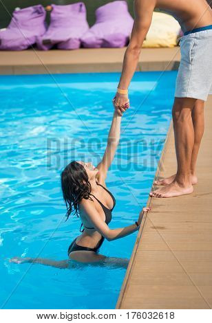 Beautiful Woman In Black Swimsuit In The Swimming Pool Holding A Man's Hand Trying To Get Out At Sun