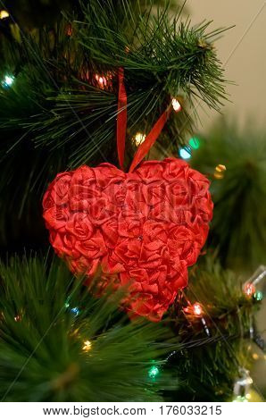 Big red heart toy on Christmas tree closeup with decoration lights on background unfocused