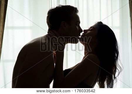 Couple near window. Woman and man in darkness. Your kiss is my remedy.