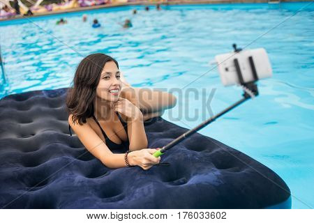 Attractive Woman In Bikini Smiling And Taking Selfie Photo On The Phone With Selfie Stick On A Mattr