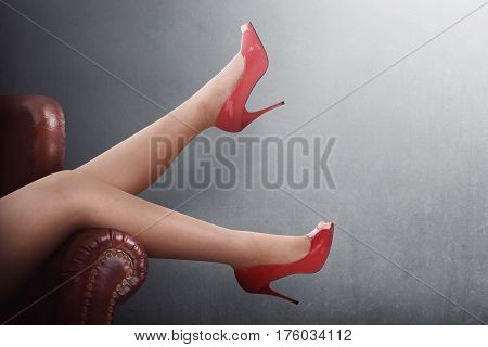 Sexy Woman Legs In Red High Heels On A Couch