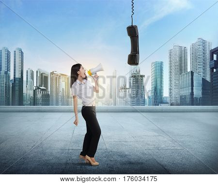 Beautiful Asian Business Woman With Bullhorn Screaming To Receiver