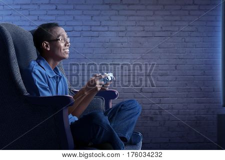 Happy Asian Nerd Man In Sofa With Gamepad Playing Game