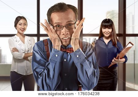 Geeky asian businessman standing in front of his team working at office