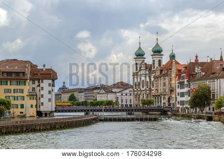 View of embankment of Reuss river with Jesuit Church in Lucerne Switzerland