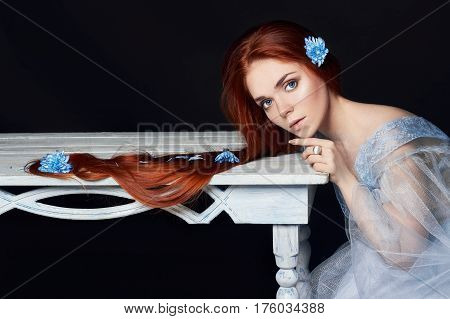 Sexy beautiful redhead girl with long hair. Perfect woman portrait on black background. Gorgeous hair and deep eyes. Natural beauty clean skin facial care and hair. Strong and thick hair. Wood table