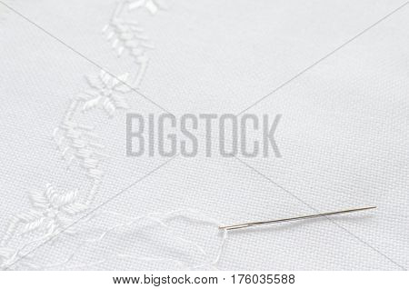 Texture of linen fabric with embroidery by flat stitch. Needle and white silk threads. Macro handmade embroidery.