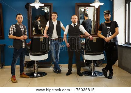 Team of young professional barbers posing to camera inside modern barbershop. Four masculine male hairstylists standing indoors at workplace in hair salon