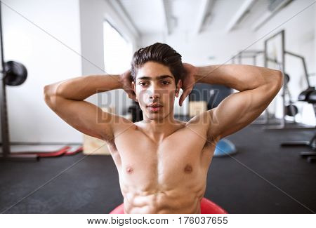 Fit hispanic man at abdominal crunch muscles exercises on fitness ball during training in fitness gym.