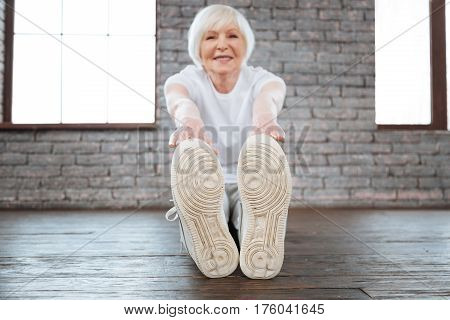 Be positive. Beautiful mature female person sitting on the floor while touching her feet keeping smile on her face