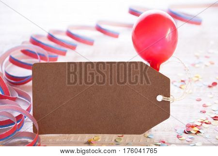 One Label With Copy Space For Advertisement. Party Decoration Like Streamer, Confetti And Balloon. Wooden Background With Vintage, Retro Or Rustic Syle